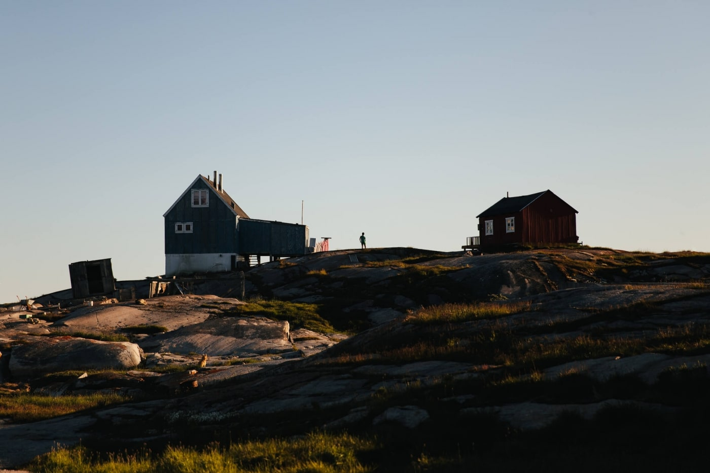 Boy stands between two homes in Oqaatsut magic hour. Photo by Jessie Brinkman Evans - Visit Greenland