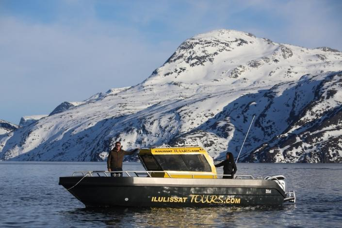 Ilulissattours boat sailing in front of mountain covered in snow in Winter. Photo by Ilulissat Tours