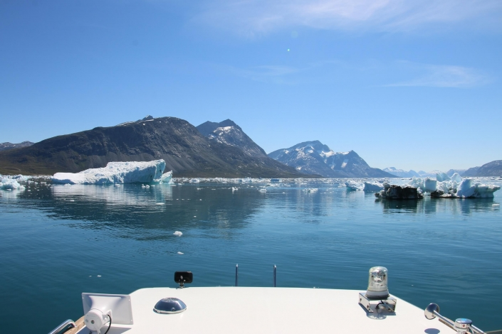 Boat sailing among icebergs in Nuup Kangerlua in summer. Photo by Nuuk Bay Adventues