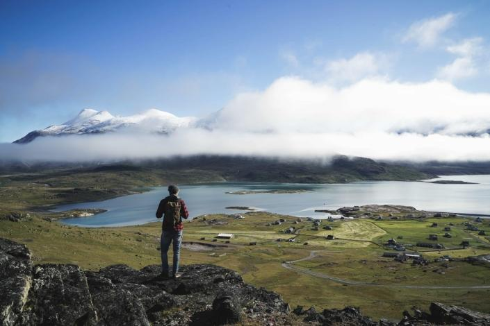 Hiker standing on rock looking at the settlement in front of him in South Greenland. Photo by Guide to Greenland, Visit Greenland