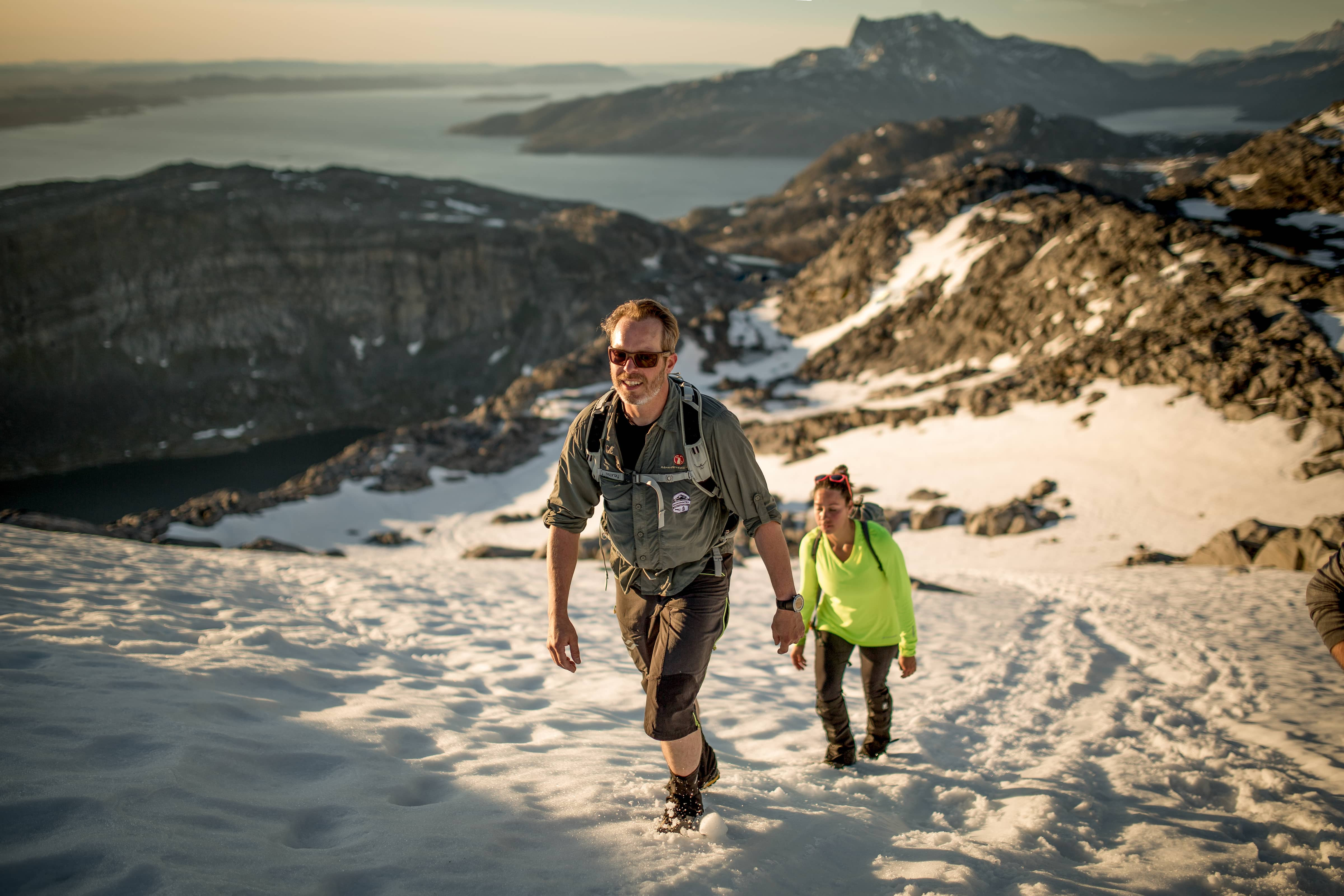 Two hikers on a slope of summer snow ascending Ukkusissaq - Store Malene outside Nuuk in Greenland