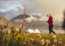 Female tourist looking at phone in Inneruulalik South Greenland by Photo by Peter Lindstrøm, Visit Greenland