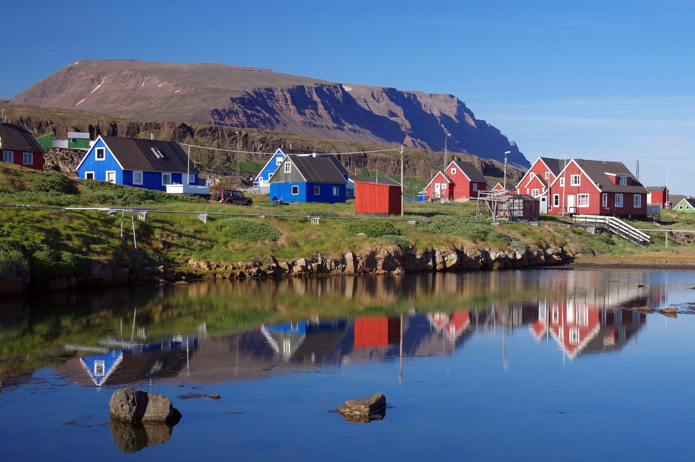 Houses of Qeqertarsuaq and the mountain behind with Lyngmark glacier on top. Photo by Reinhard Pantke - Visit Greenland