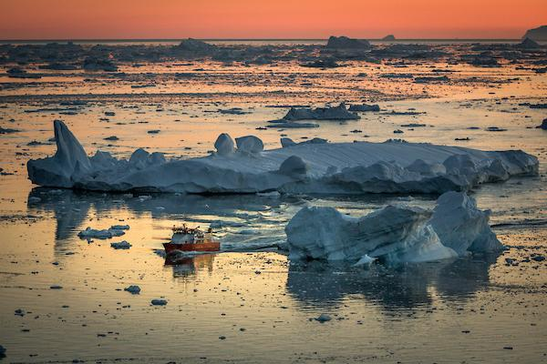 A small passenger boat in the sunset near Ilulissat in Greenland. Photo by Mads Pihl - Visit Greenland