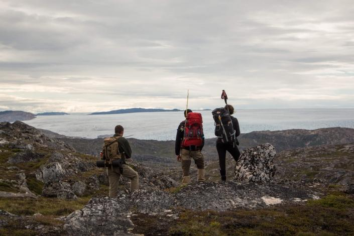 Hikers taking a break to observe the mountains and icecap surrounding them.