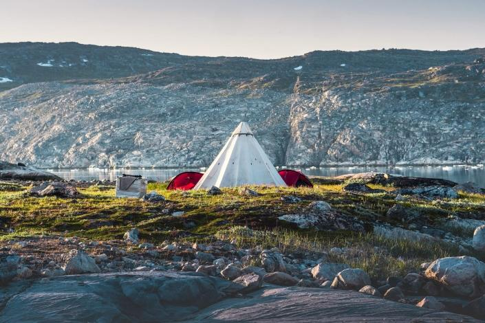 Camp setup near a mountain at the waterfront .