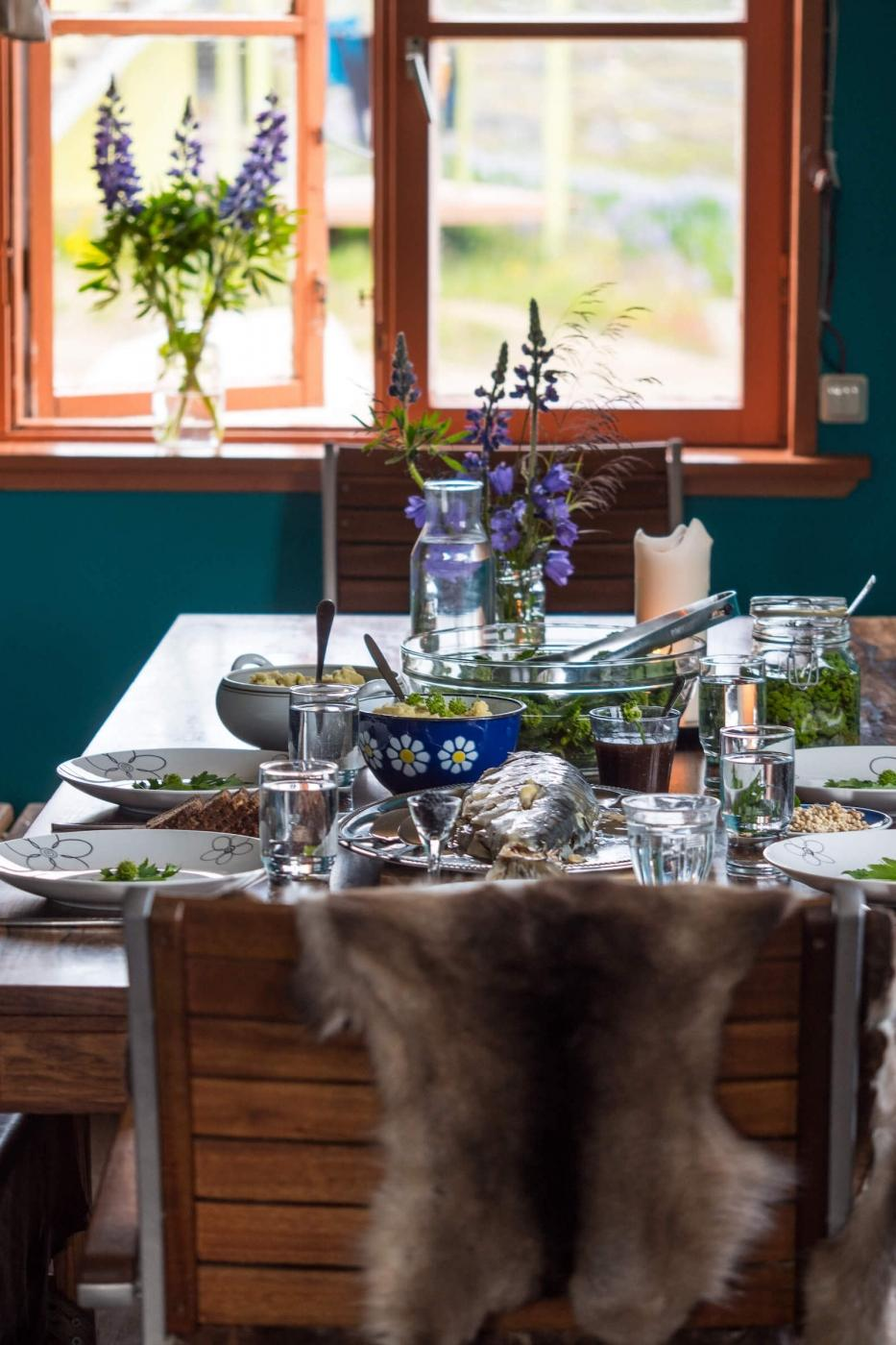 Dinner table with freshly caught fish and a side of local vegetables, plants and herbs.