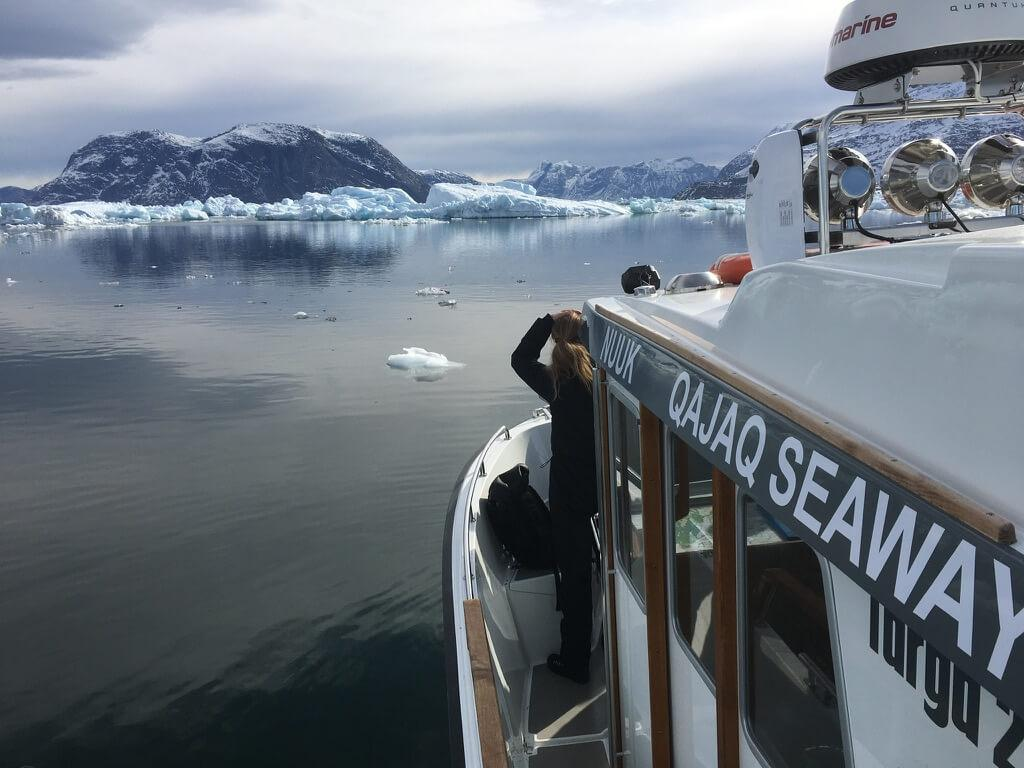 View from the top of the boat of passengers looking over icebergs and mountains. Photo by Qajaq Seaway