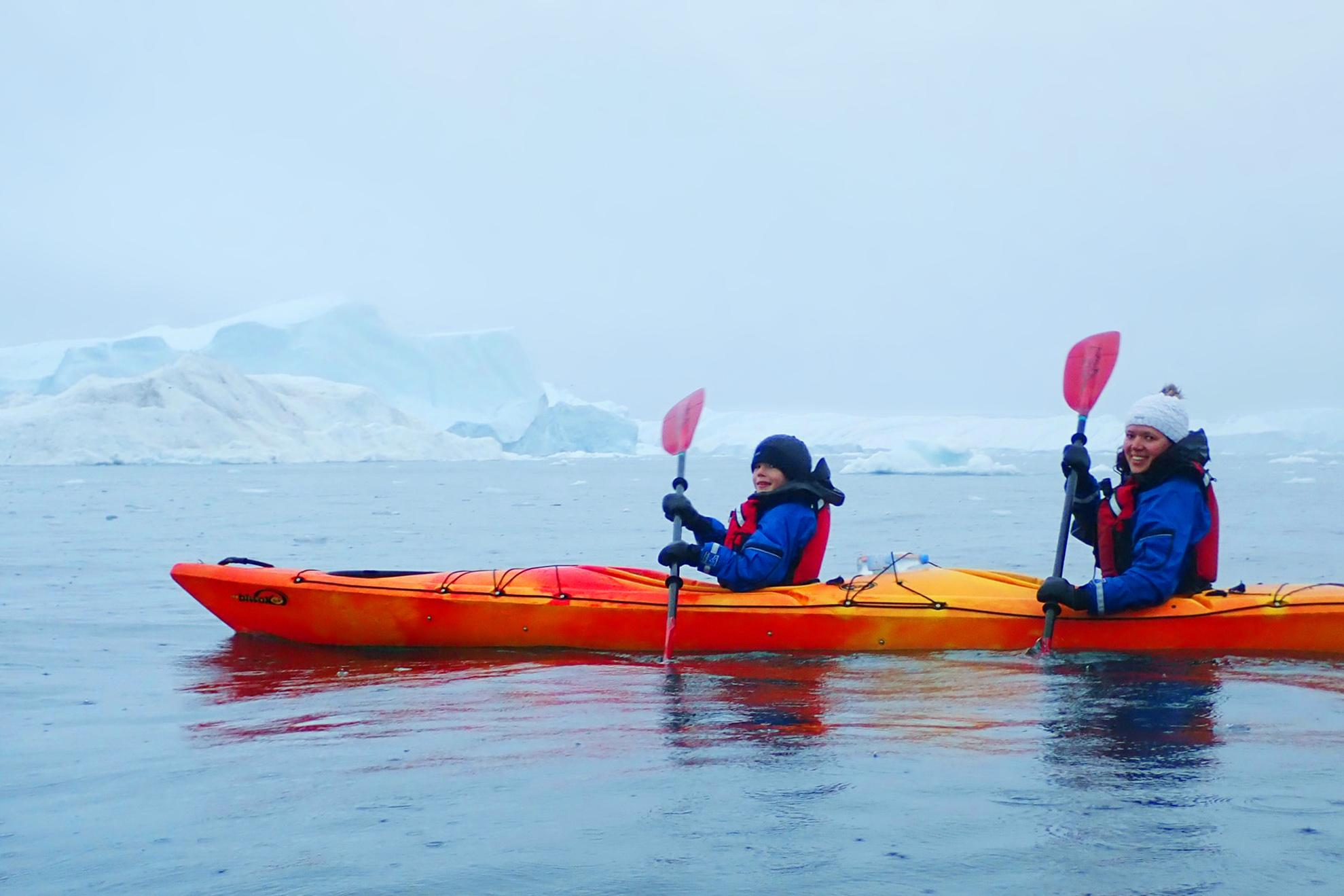 Family kayaking between icebergs in Greenland. Photo by Jurga Rubinovaite. Visit Greenland
