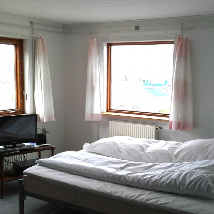 A cozy bedroom with a tv and large windows. to enjoy the view. Photo by Aasiaat Guesthouse