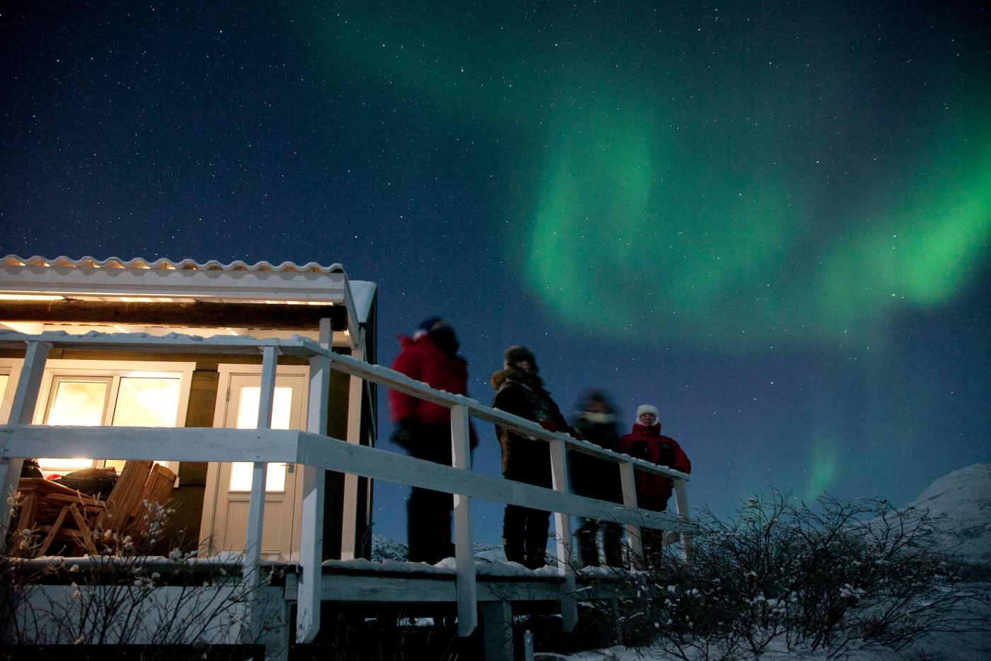Kangerlussuaq northern lights at a hut. Photo - David Trood, Visit Greenland