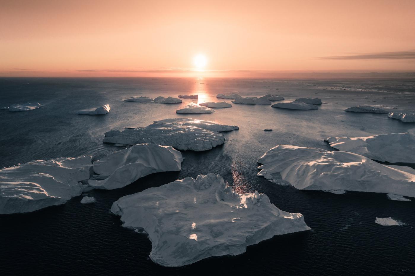 Sun aligned with icebergs in Ilulissat. Photo - Ben S. Rehn, Visit Greenland