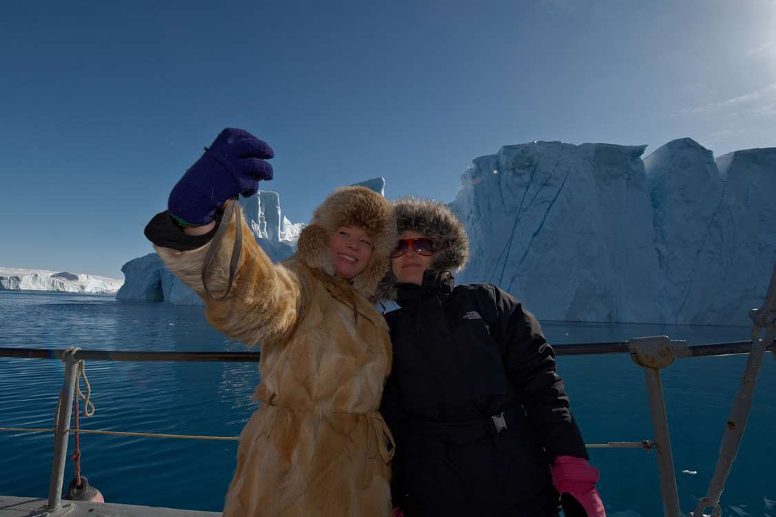 Two people taking a selfie infront of an iceberg. Photo by Thomas Eltorp, Visit Greenland