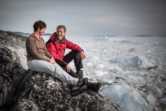 A couple on the shores of the Ilulissat ice fjord in Greenland. Photo by Uummannaq