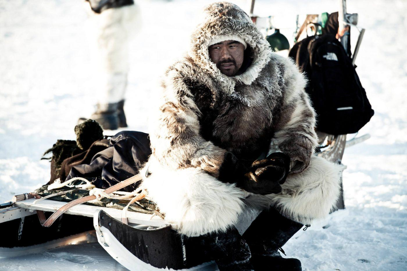 A dog sled driver from Ilulissat wearing fur and skin clothes in Greenland, by Andre Schoenherr