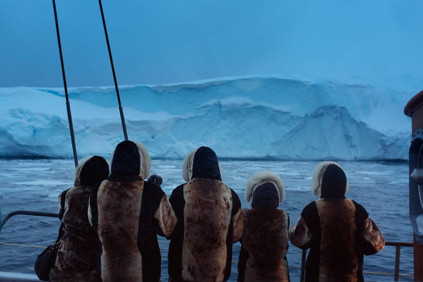 A group of seal skin dressed tourists enjoying the Ilulissat icefjord during blue hour in Greenland. Photo by Rebecca Gustafsson - Visit Greenland