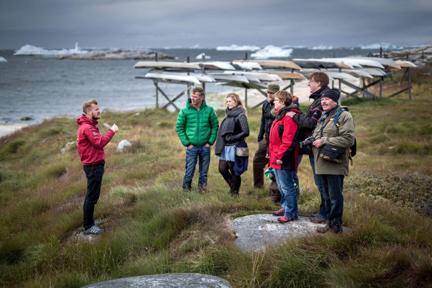 A guided walk in Ilulissat with traditional Greenland kayaks in the background. Photo by Mads Pihl