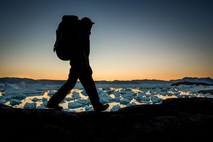 A hiker along the shores of Sermilik Ice Fjord near Tiniteqilaaq in East Greenland. By Mads Pihl
