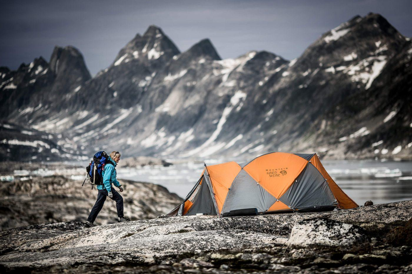 A hiker approaching a tent at a camp in East Greenland near Tasiilaq. By Mads Pihl