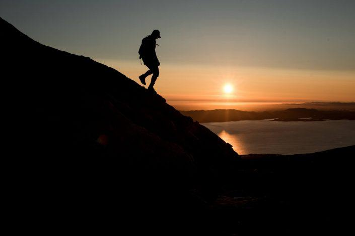 A hiker descending the mountain Ukkusissaq - Store Malene in the midnight sun outside Nuuk in Greenland