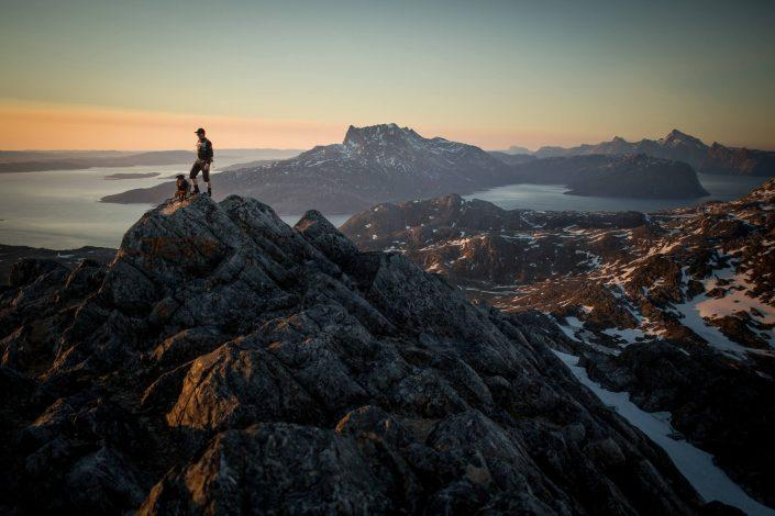 A hiker on Ukkusissaq - Stroe Malene in the midnight sun overlooking Sermitsiaq near Nuuk in Greenland. By Mads Pihl