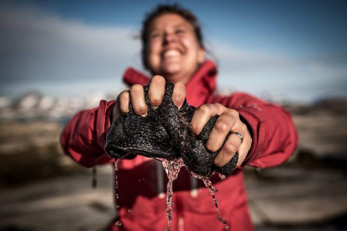A hiker washing socks in a trek in East Greenland. Photo by Mads Pihl