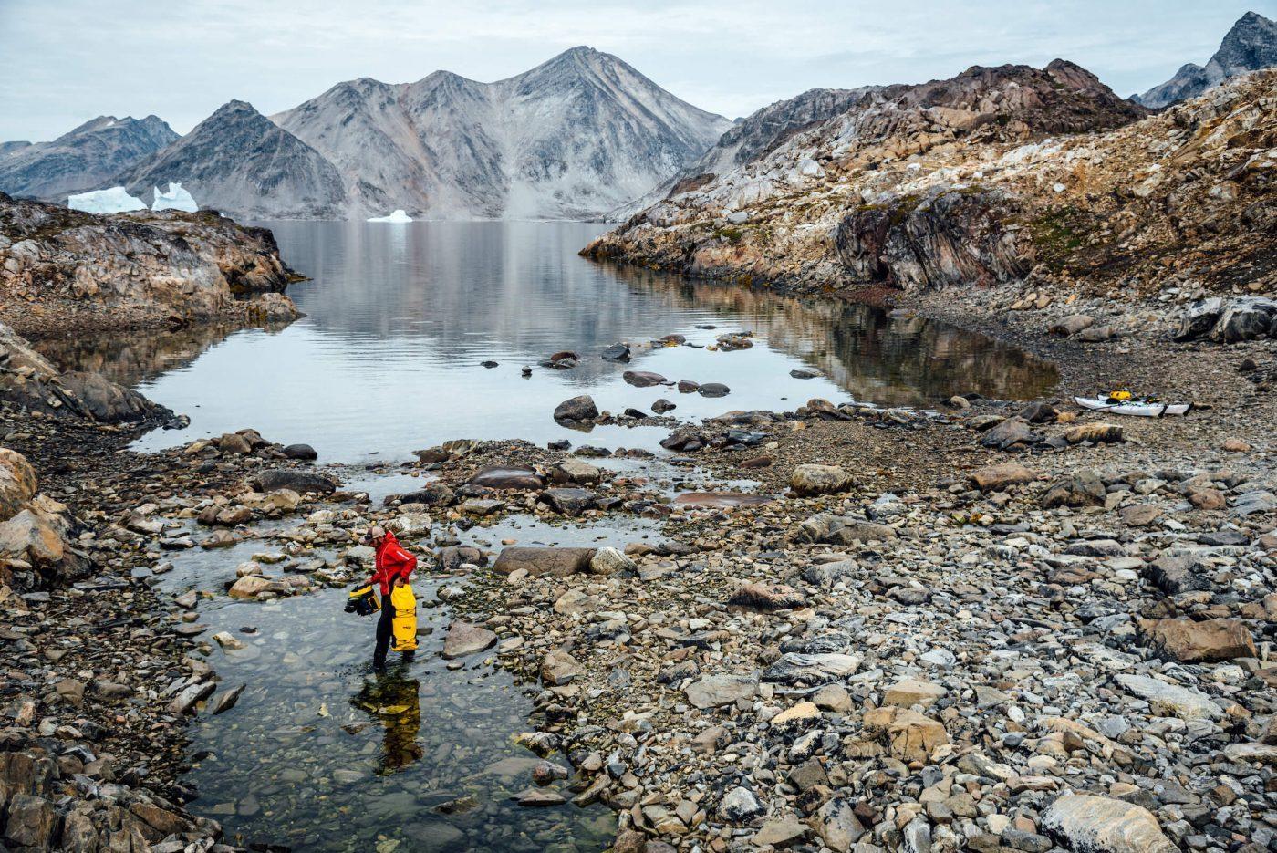 A kayaker walks along the shore with gear, Between Kulusuk & Kuummiut. By Chris Brinlee Jr