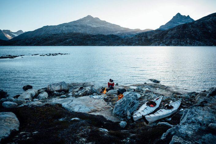 A kayaker with boats has a driftwood fire along shoreline, Camp In Tasiilaq Fjord. By Chris Brinlee Jr