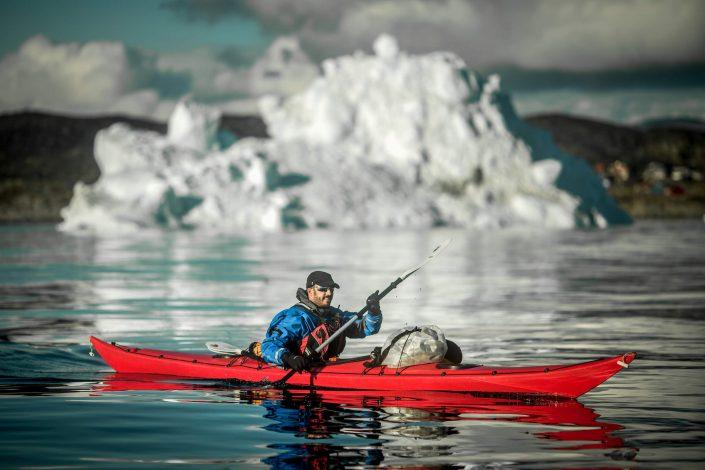 A PGI Greenland kayaking guide in front of an iceberg in the Disko Bay in Greenland. By Mads Pihl