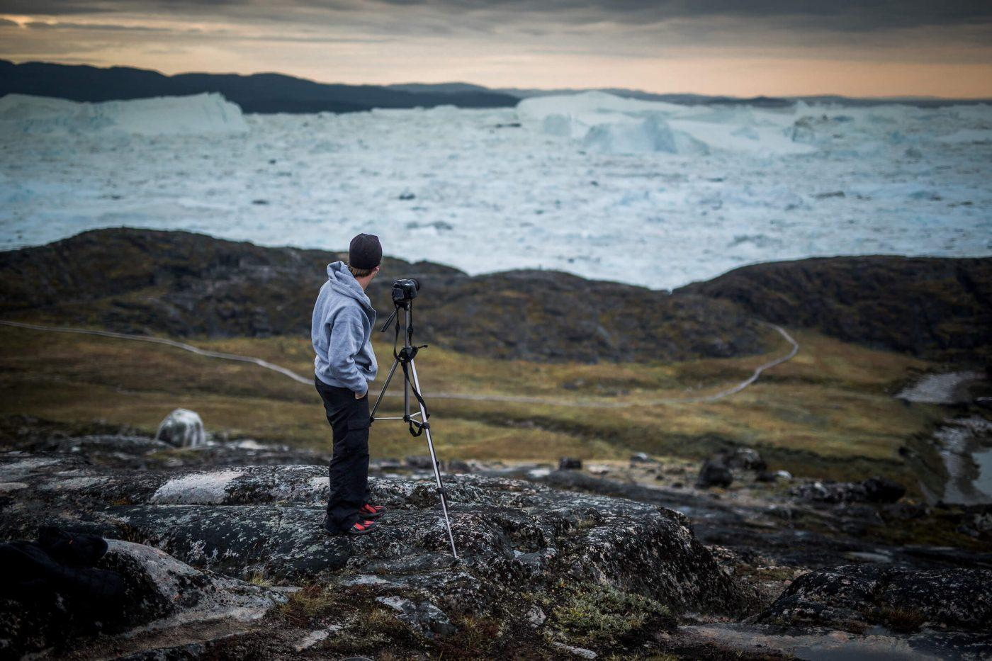 A photographer near the Ilulissat ice fjord in Greenland. By Mads Pihl