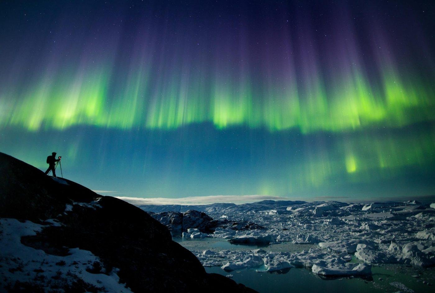 A photographer on a photo tour in North Greenland captures the perfect nighttime shot of northern lights, the starry night sky, and icebergs in the Ilulissat Icefjord. Photo by Paul Zizka.