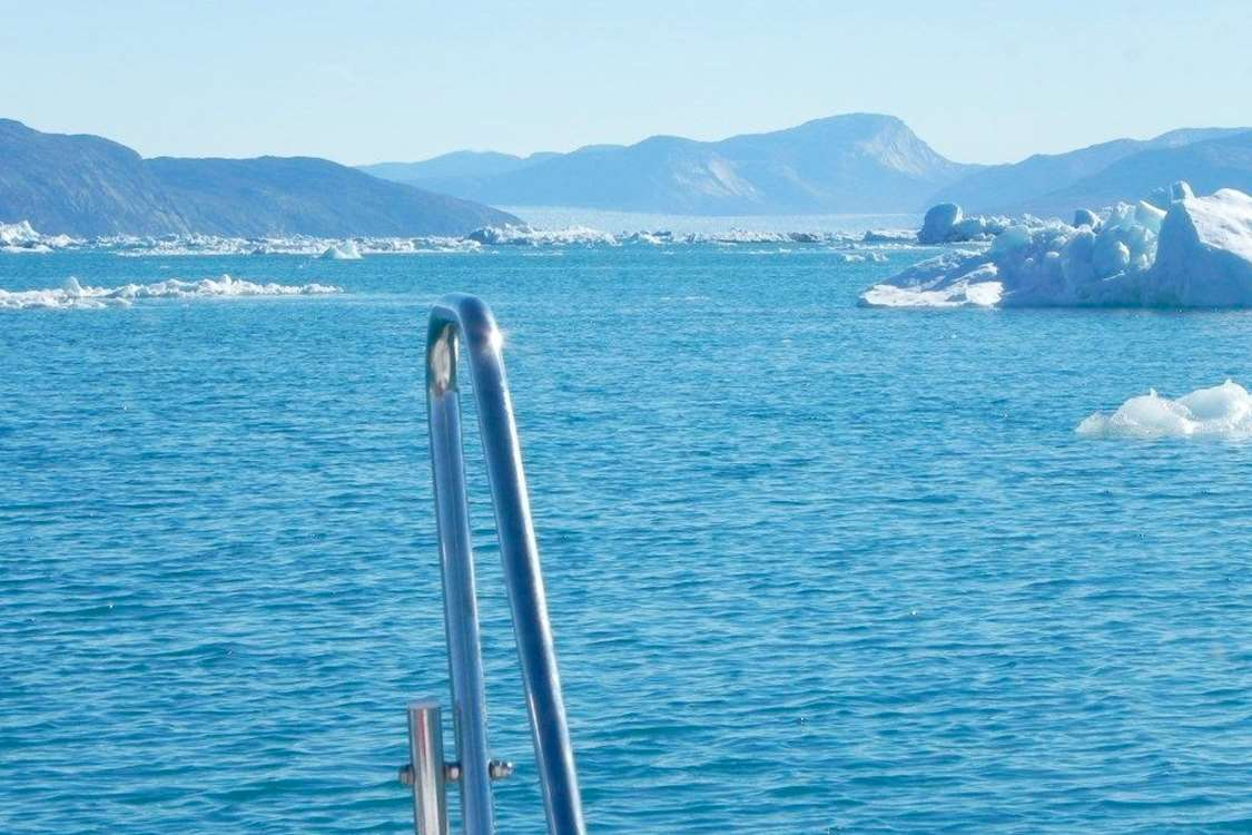 View of icebergs and sea on a sunny day in Nuuk Fjord. Photo by Asimut Tours and Camp