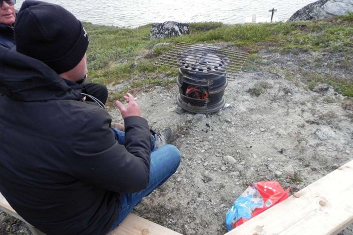 Tourist and guide using a homemade grill in Kapisillit, close to Nuuk. Photo by Asimut Tours and Camp