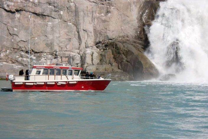 Passenger boat approaching waterfall. Photo by Blue Ice Explorer, Visit Greenland.