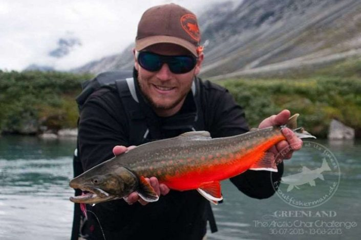 Man holding an arctic char in the fjords of Greenland. Photo by Bowhunting Greenland, Visit Greenland.