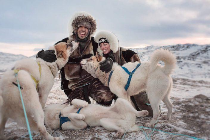 Canadian social media influencers Siya Zarrabi and Kristen Sarah being greated by sled dogs near Ilulissat in Greenland. Photo by Rebecca Gustafsson