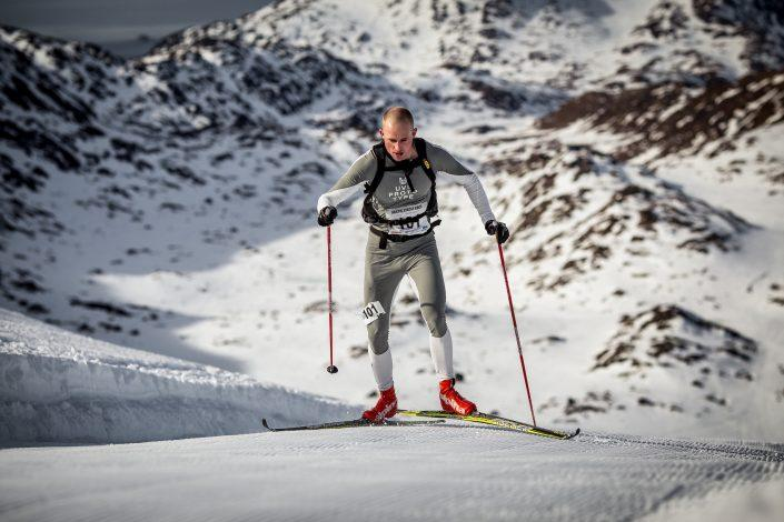 A skier in the Arctic Circle Race running uphill near Sisimiut in Greenland