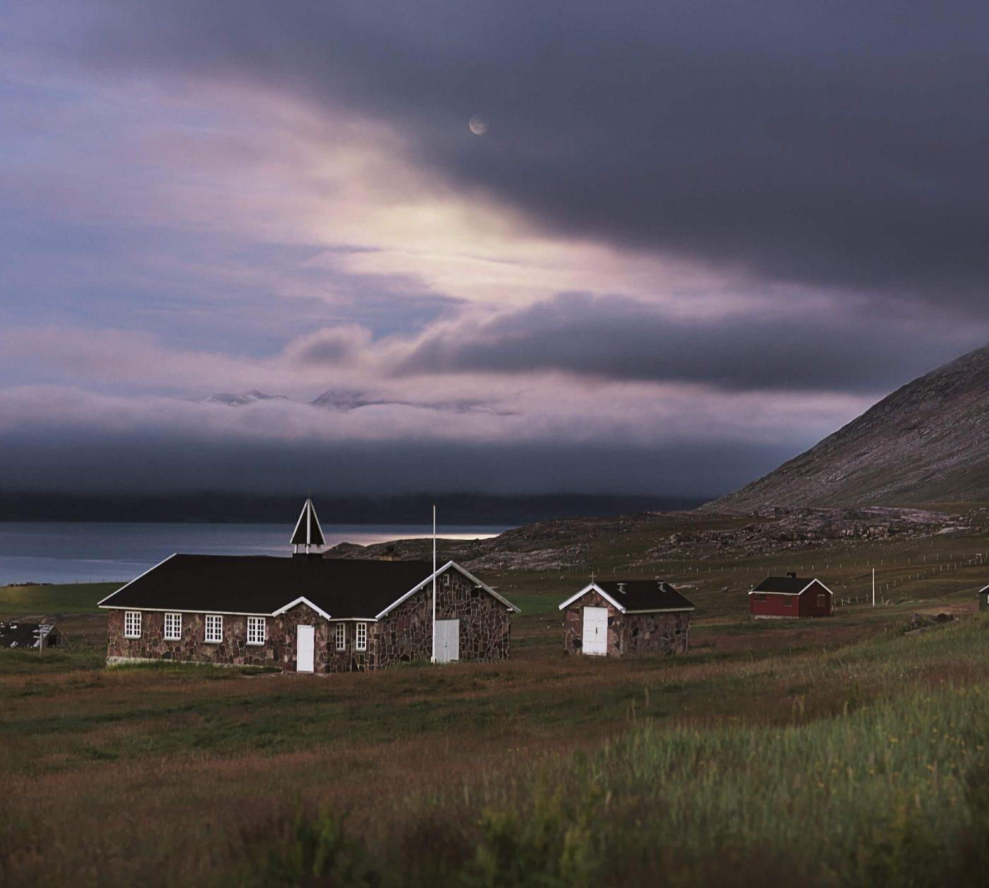 Dark clouds with a silver lining over the church in Igaliku in South Greenland. Photo by David Trood