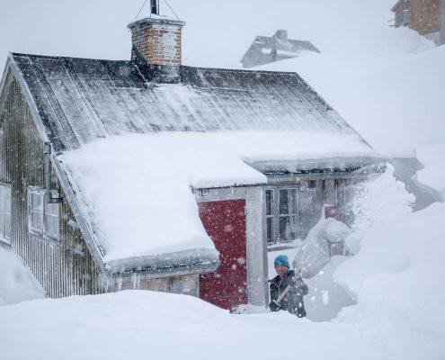 Digging a house out of the deep snow in Kuummiut in East Greenland. Photo by Mads Pihl
