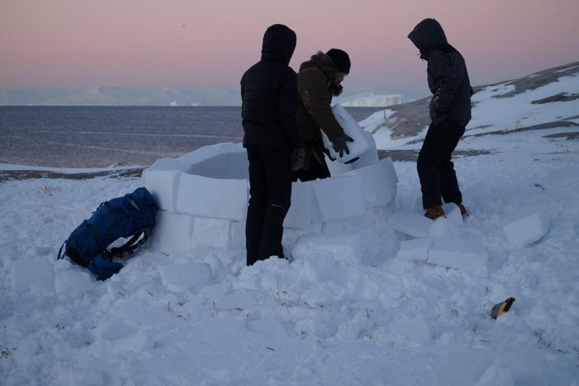 Guide and tourists building an iglo in North Greenland. Photo by Diskobay Adventures