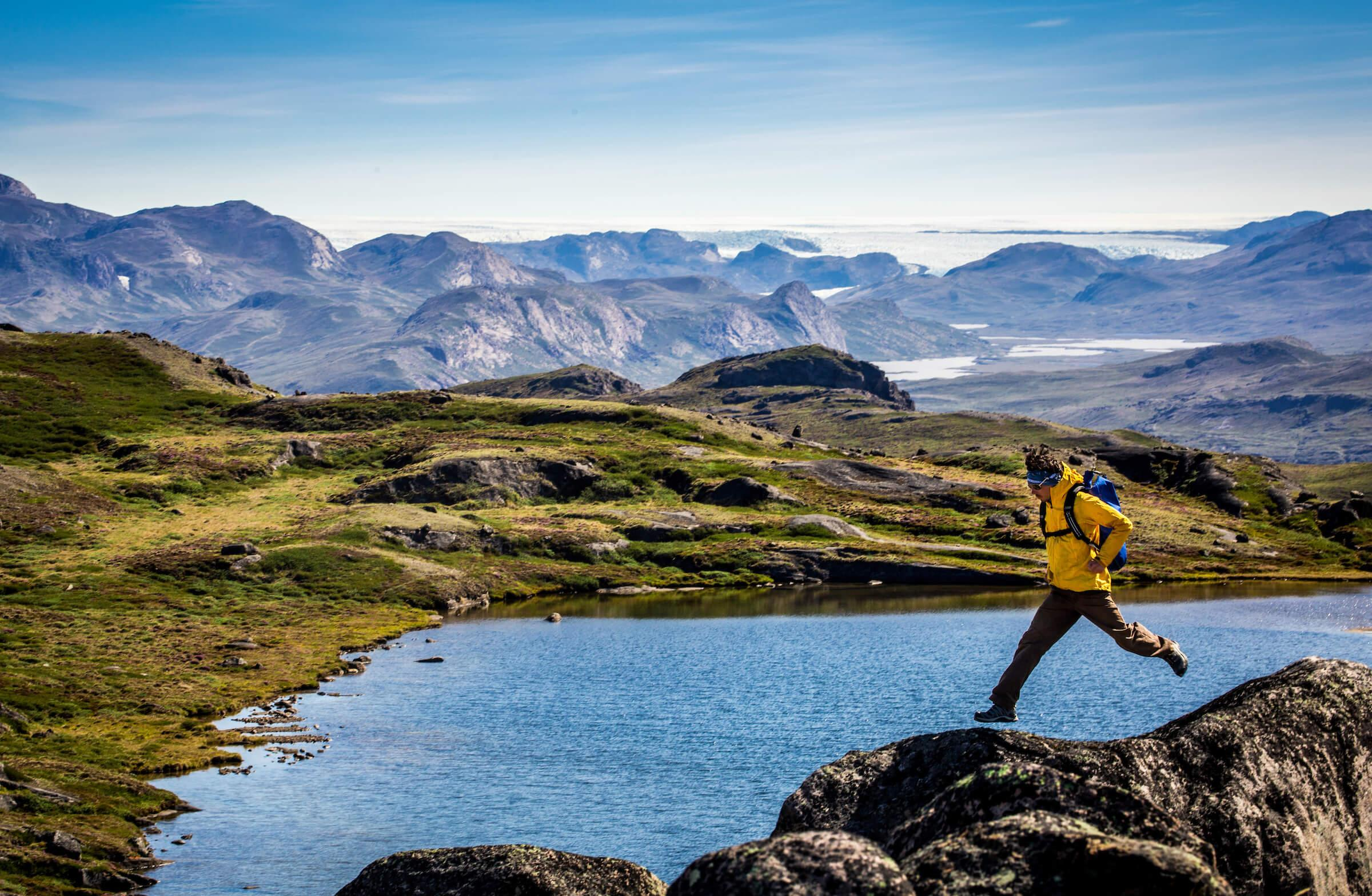Enthusiastic hiker having fun near the Greenland Ice Sheet along the Arctic Circle. By Raven Eye Photography