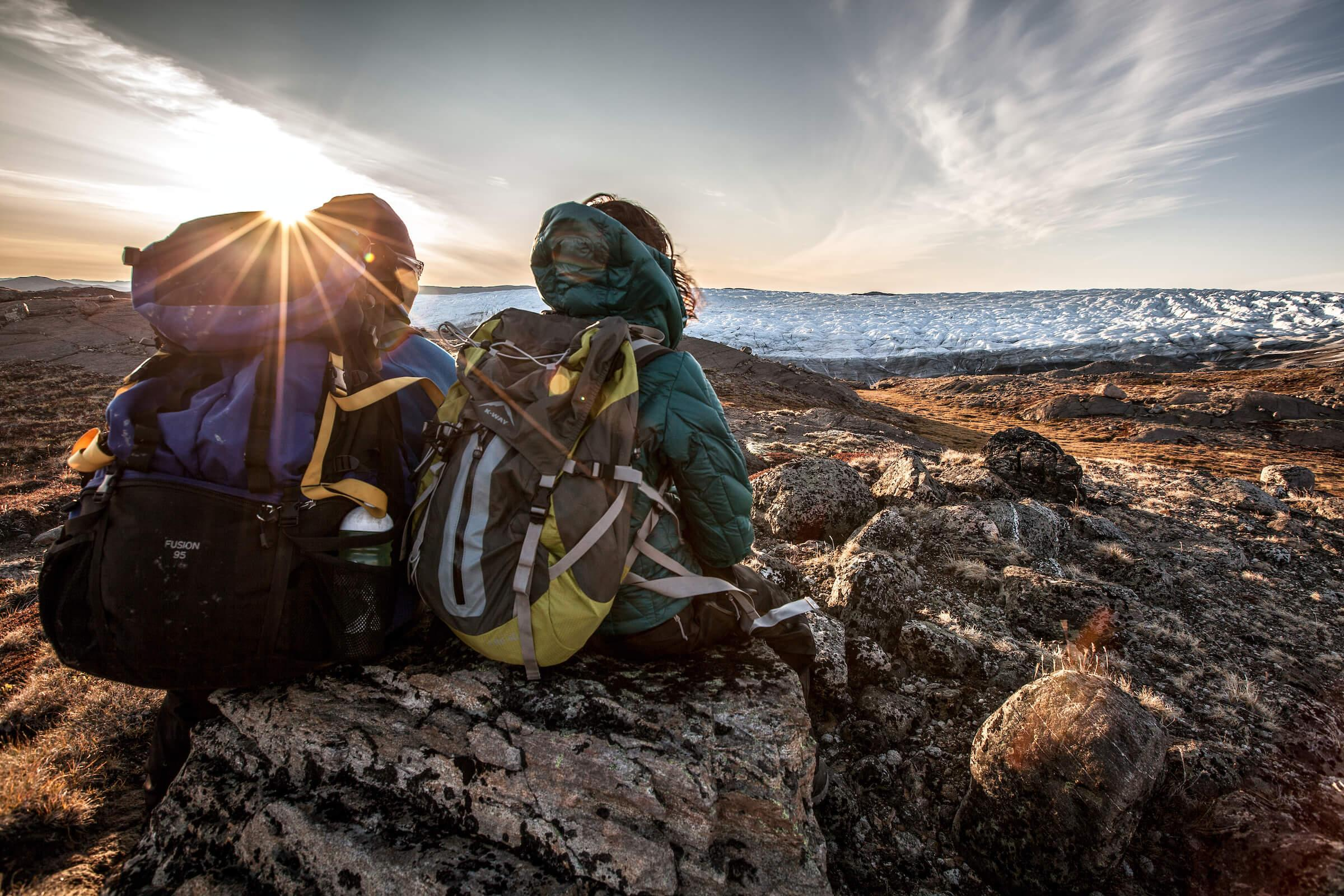 Two hikers enjoying the sunset over the edge of the Greenland Ice Sheet near Kangerlussuaq. By Mads Pihl