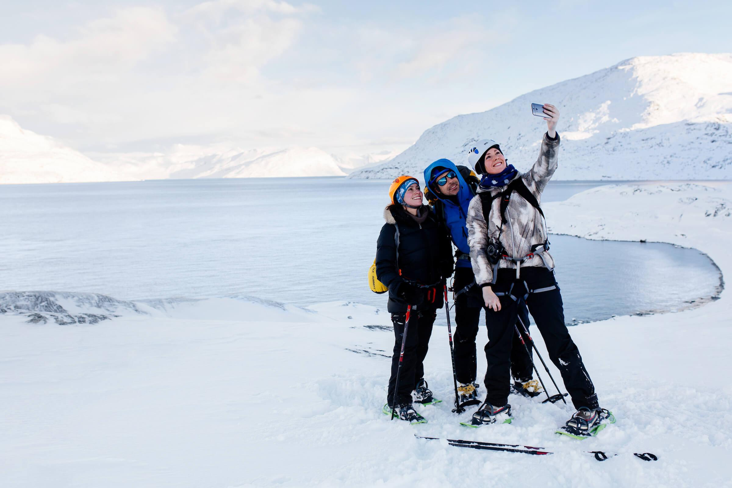 Female tourists taking a selfie with Marc Carreras on winter hike in Nuuk in Greenland. By Rebecca Gustafsson