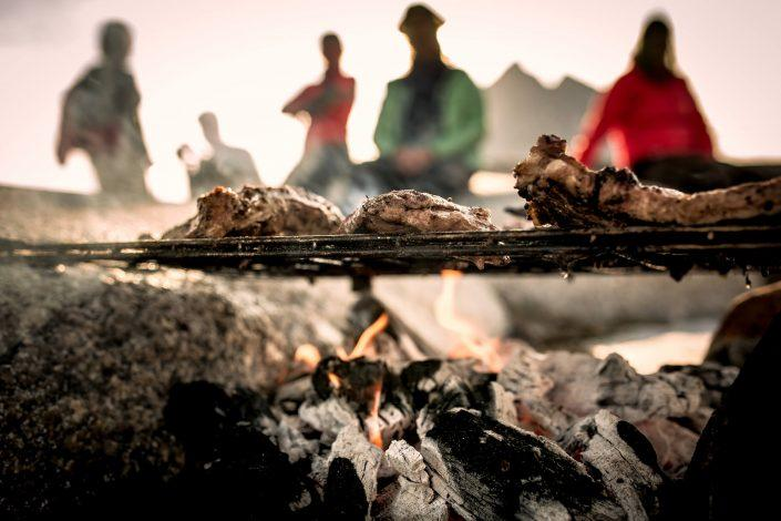 Food roasting over a fire in East Greenland. Photo by Mads Pihl