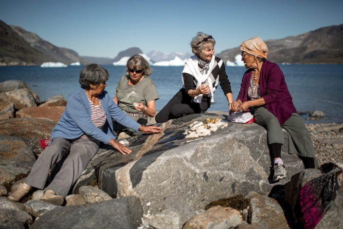 Four women enjoying a traditional meal of arctic charr and vegetables on the rocks in Narsaq in South Greenland. By Mads Pihl