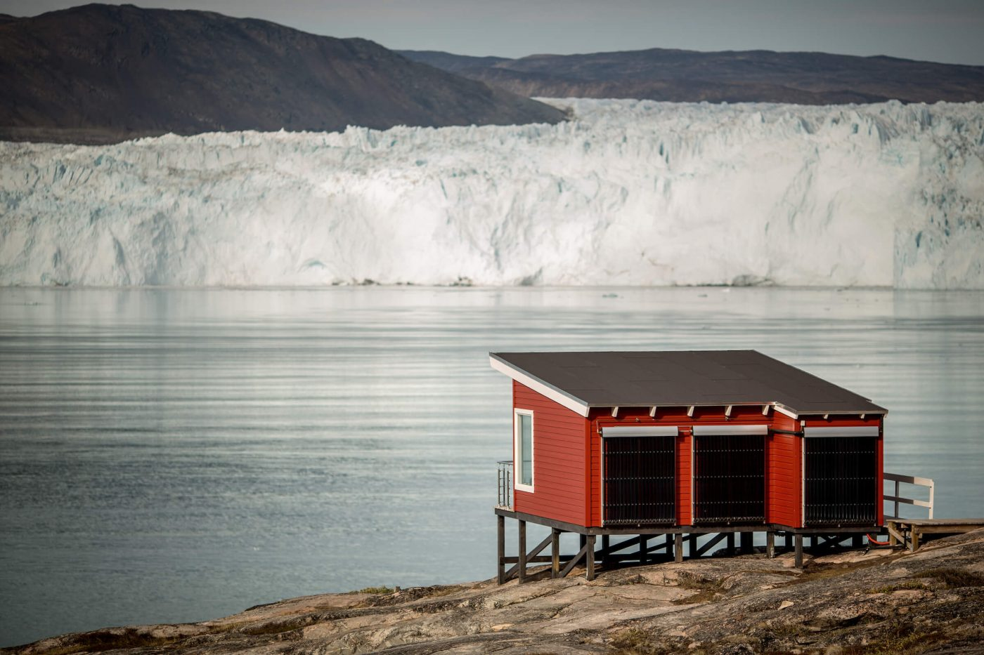 A comfort hut at Eqi Glacier Lodge with the glacier in the background in North Greenland. Photo by Mads Pihl, Visit Greenland