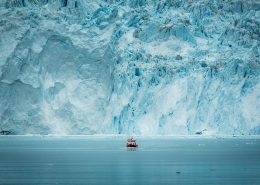 Glaciers a small passenger boat in front of the huge glacier wall at the Eqi glacier in Greenland. Photo by Mads Pihl