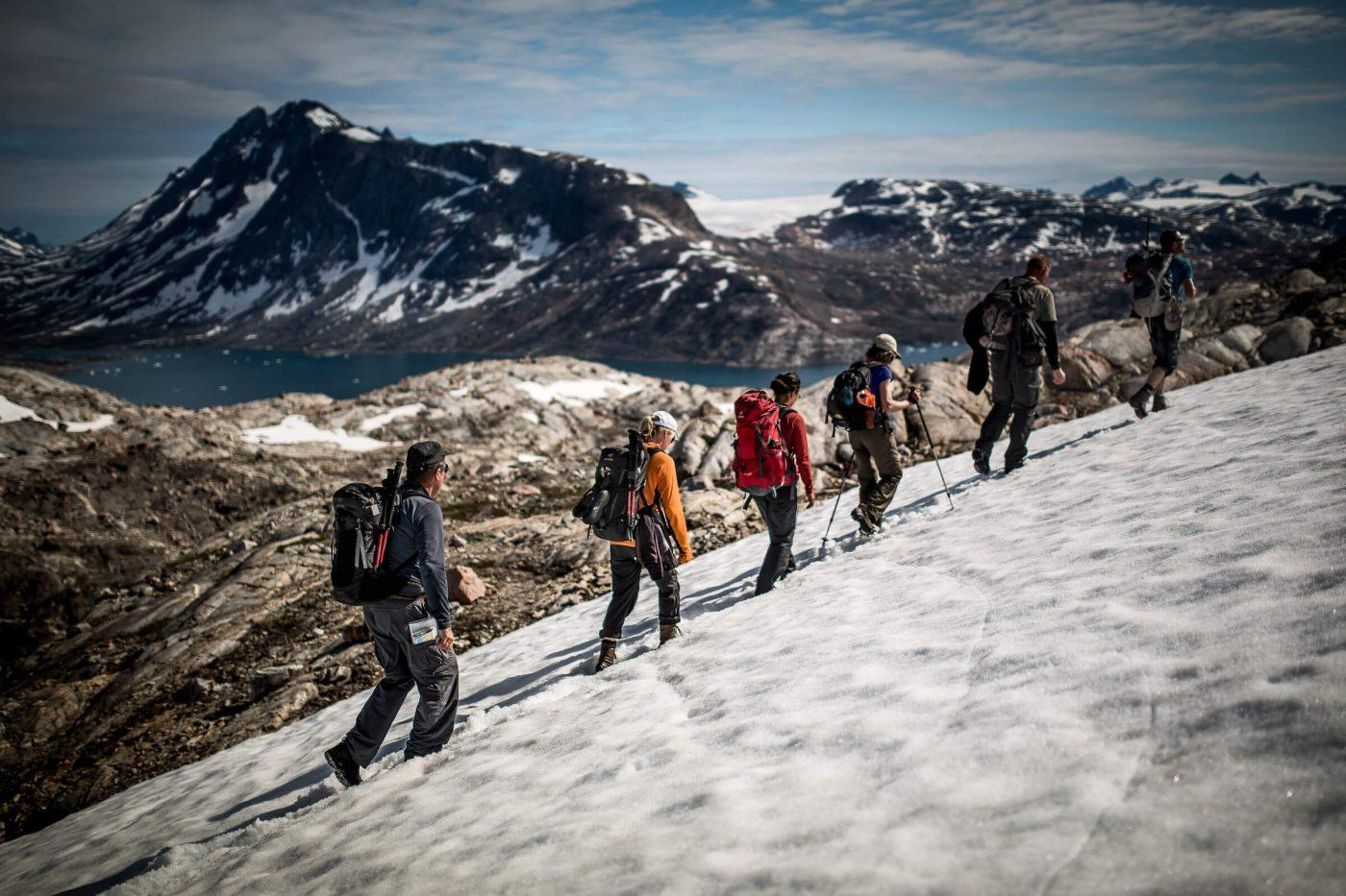Greenland Travel hikers passing through lingering snow on the mountain near Tiniteqilaaq in East Greenland. By Mads Pihl