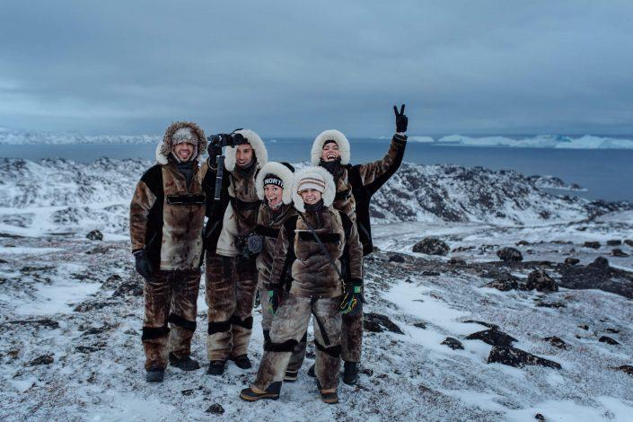 Group photo of social media influencers wearing seal skin clothes in front of a view point near Ilulissat in Greenland. Photo by Rebecca Gustafsson