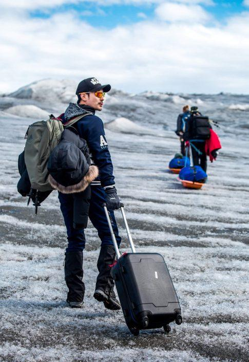 A lesson in inaprorpriate luggage in Greenland - rolling suitcases are not ideal for glacier walking on the Greenland Ice Sheet. Photo by Raven Eye Photography